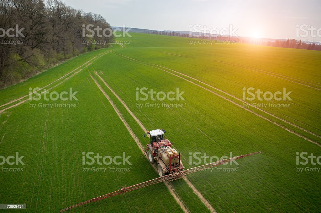 Aerial view of the tractor moving along the track at sunset stock photo