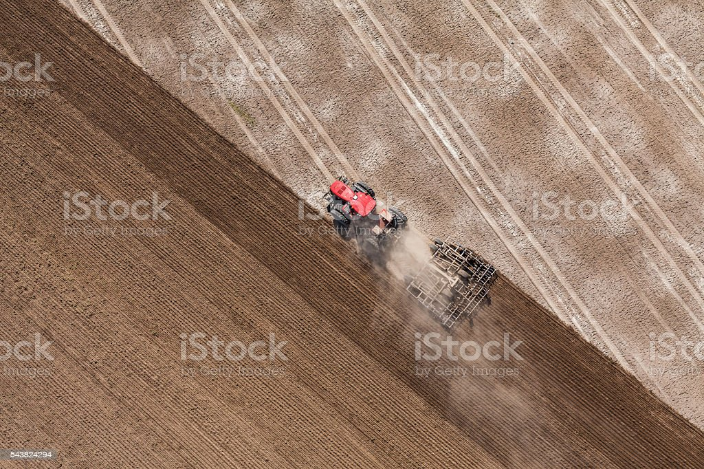 aerial view of the tractor working on the harvest field stock photo
