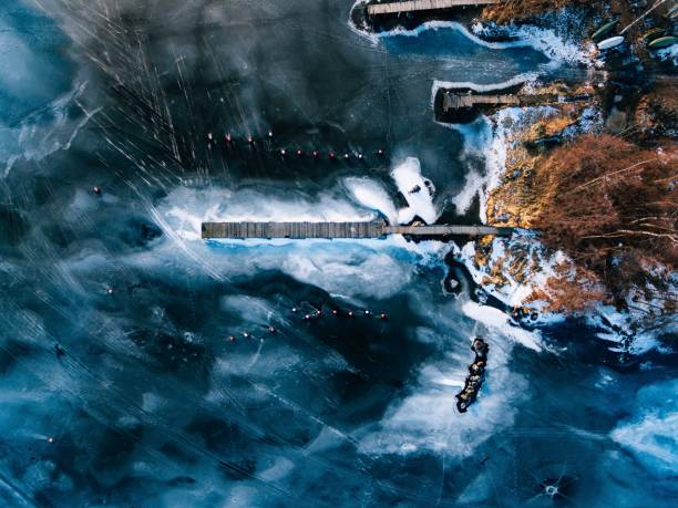 Aerial view of the winter frozen lake with wooden piers captured with a drone in Finland. - foto stock