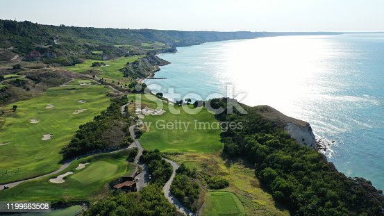 Aerial view of Thracian cliffs golf and beach resort. Beautiful landscape with green hills, meadows, fields for golf, road, hotels and trees near the shore of Black sea, Bulgaria. Summer sunny day.