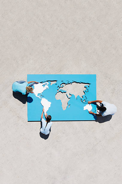 Aerial View of three people doing world map puzzle outdoors stock photo