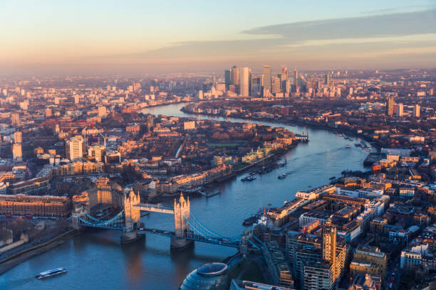 Aerial view of Tower Bridge and Canary Wharf skyline at sunset stock photo