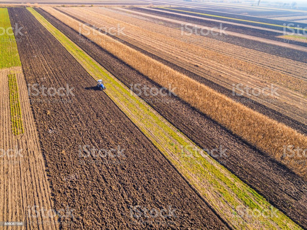 Aerial view of tractor ploughing the field stock photo