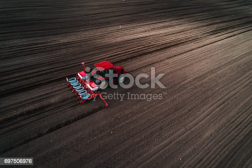 istock Aerial view of tractor seeding field. Farmer preparing land with seedbed cultivator 697506976