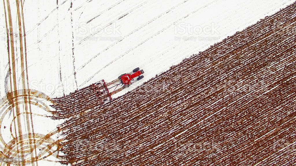 Aerial view of tractor tilling snow covered field in Winter. stock photo