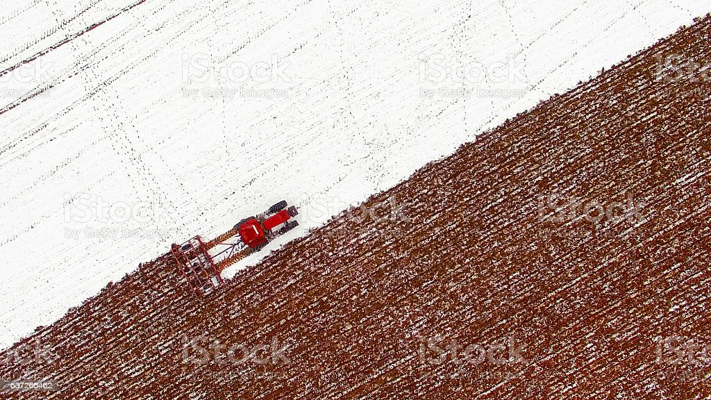 Aerial view of tractor tilling snow covered field stock photo