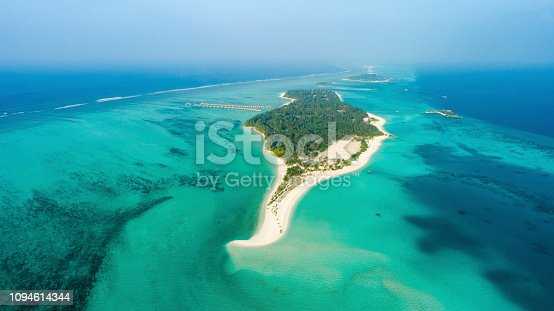 Aerial view of sandy beach and lush vegetation on tropical island surrounded by vast tranquil ocean,Maldives