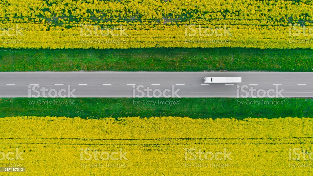 Aerial view of truck on  highway  near the yellow field of rapeseed stock photo