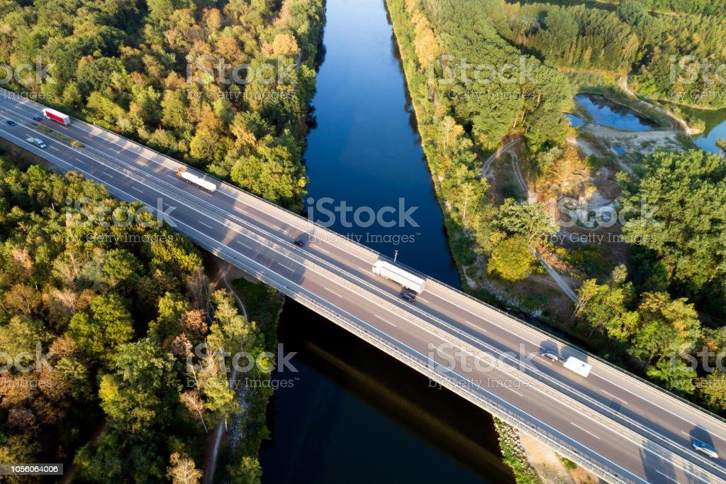 Luftaufnahme von LKW und Pkw auf Autobahn Brücke über Fluss – Foto