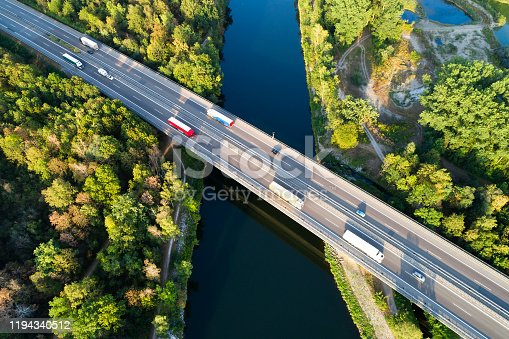 Trucks and cars on highway bridge over river, aerial view, Baden Wurttemberg, Germany.