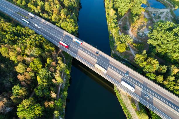 Luftaufnahme von Lastwagen und Autos auf Autobahnbrücke über Fluss – Foto