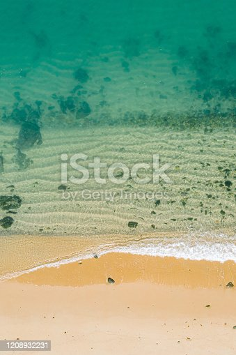 999001484 istock photo Aerial view of turquoise ocean wave reaching the coastline 1208932231
