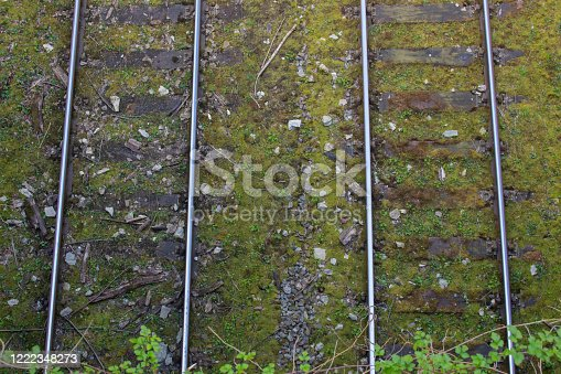Top view of two parallel railway tracks with old wooden railroad sleepers and moss, aerial view