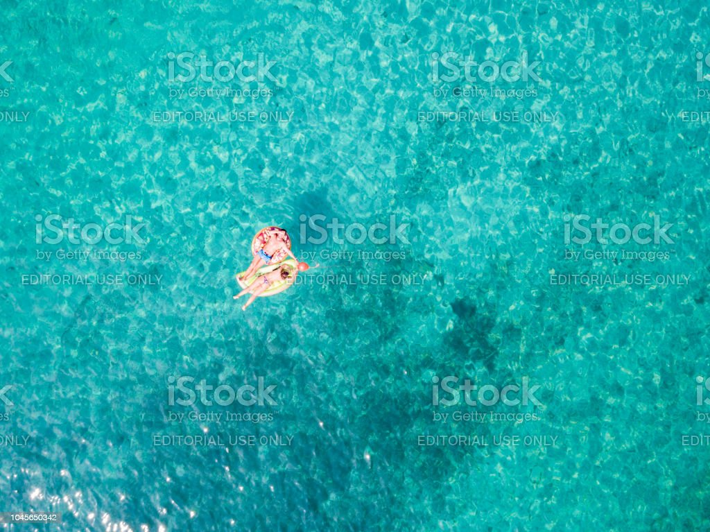 Aerial view of two people relaxed on an inflatable mat floating on a...