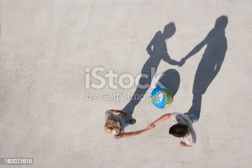 istock Aerial View of two people shaking hands with shadow and globe outdoors 182021615