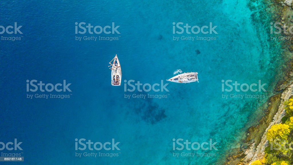 Aerial view of two sailing boats anchoring next to reef стоковое фото