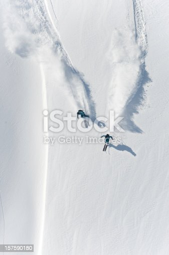 istock Aerial view of two skiers skiing downhill in powder snow 157590180
