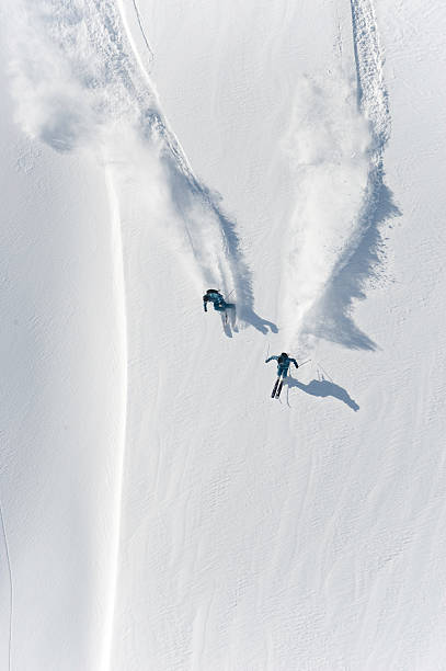 Aerial view of two skiers skiing downhill in powder snow stock photo