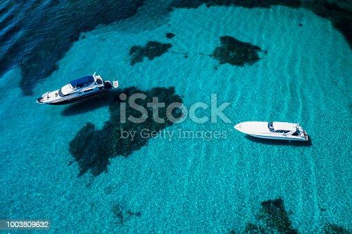 1066331604istockphoto Aerial view of two yachts on an emerald and transparent Mediterranean sea. Emerard coast (Costa Smeralda), Sardinia, Italy. 1003809632