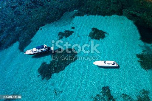 1066331604istockphoto Aerial view of two yachts on an emerald and transparent Mediterranean sea. Emerard coast (Costa Smeralda), Sardinia, Italy. 1003809640