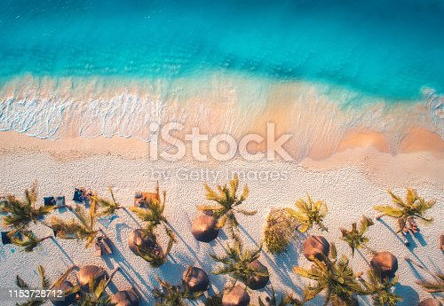1136453253 istock photo Aerial view of umbrellas, palms on the sandy beach of blue sea at sunset. Summer travel in Zanzibar, Africa. Tropical landscape with palm trees, parasols, people, sand, waves. Top view from the air 1153728712