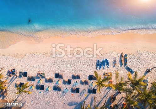 1136453253 istock photo Aerial view of umbrellas, palms on the sandy beach of blue sea at sunset. Summer travel in Zanzibar, Africa. Tropical landscape with palm trees, parasols, people, sand, waves. Top view from the air 1153728714