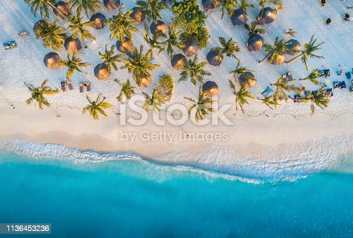 1136453253 istock photo Aerial view of umbrellas, palms on the sandy beach of Indian Ocean at sunset. Summer holiday in Zanzibar, Africa. Tropical landscape with palm trees, parasols, white sand, blue water, waves. Top view 1136453236
