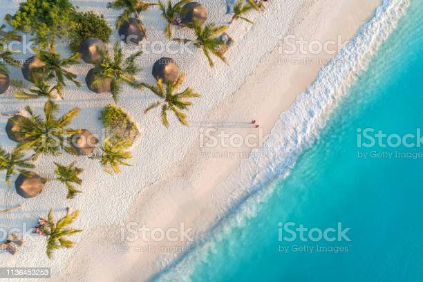 Photo of Aerial view of umbrellas, palms on the sandy beach of Indian Ocean at sunset. Summer holiday in Zanzibar, Africa. Tropical landscape with palm trees, parasols, white sand, blue water, waves. Top view