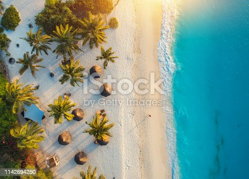 istock Aerial view of umbrellas, palms on the sandy beach of Indian Ocean at sunset. Summer holiday in Zanzibar, Africa. Tropical landscape with palm trees, parasols, white sand, blue water, waves. Top view 1142694250