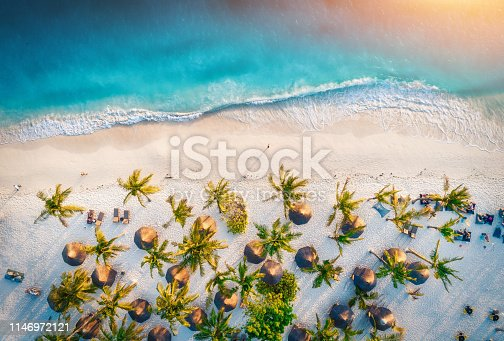 1136453253 istock photo Aerial view of umbrellas, palms on the sandy beach of Indian Ocean at sunset. Summer holiday in Zanzibar, Africa. Tropical landscape with palm trees, parasols, white sand, blue water, waves. Top view 1146972121