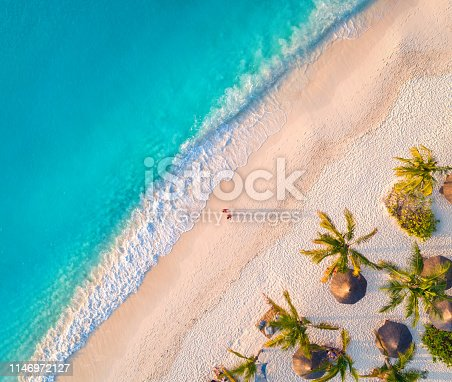 1136453253 istock photo Aerial view of umbrellas, palms on the sandy beach of Indian Ocean at sunset. Summer in Zanzibar, Africa. Tropical landscape with palm trees, parasols, walking people, blue water, waves. Top view 1146972127