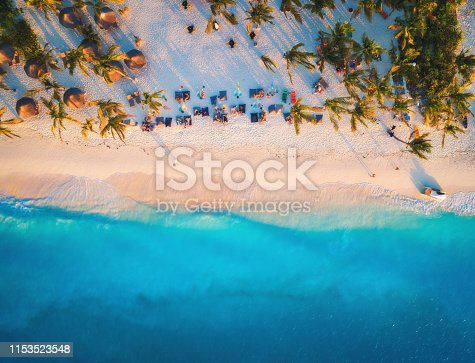 1136453253 istock photo Aerial view of umbrellas, palms on the sandy beach of Indian Ocean at sunset. Summer travel in Zanzibar, Africa. Tropical landscape with palm trees, parasols, people, sand, blue water, waves. Top view 1153523548