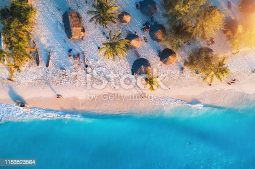 1136453253 istock photo Aerial view of umbrellas, palms on the sandy beach of Indian Ocean at sunset. Summer travel in Zanzibar, Africa. Tropical landscape with palm trees, parasols, people, sand, blue water, waves. Top view 1153523564