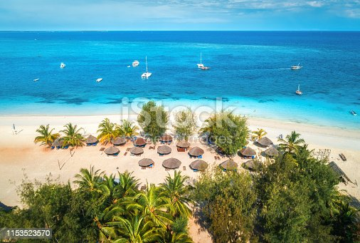 1136453253 istock photo Aerial view of umbrellas, palms on the sandy beach of Indian Ocean at sunny day. Summer holiday in Zanzibar, Africa. Tropical landscape with palm trees, parasols, boats, yachts, blue water. Top view 1153523570