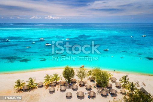1136453253 istock photo Aerial view of umbrellas, palms on the sandy beach of Indian Ocean at bright sunny day. Summer holiday in Africa. Tropical seascape with green palm trees, parasols, boats, yachts, blue water. Top view 1170506269