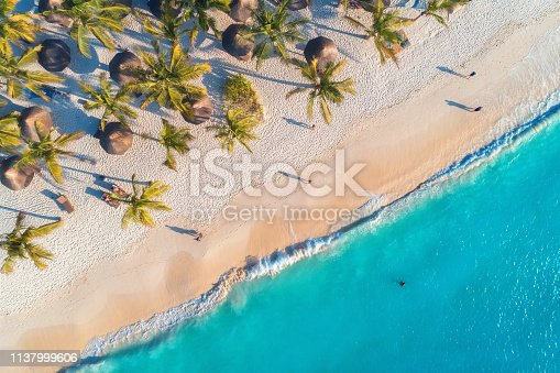 1136453253 istock photo Aerial view of umbrellas, palms on the sandy beach, people, blue sea with waves at sunset. Summer holiday in Zanzibar, Africa. Tropical landscape with palm trees, parasols, white sand, ocean. Top view 1137999606
