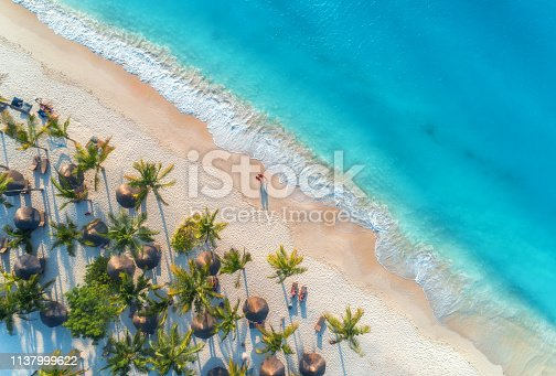 1136453253 istock photo Aerial view of umbrellas, palms on the sandy beach, people, blue sea with waves at sunset. Summer holiday in Zanzibar, Africa. Tropical landscape with palm trees, parasols, white sand, ocean. Top view 1137999622