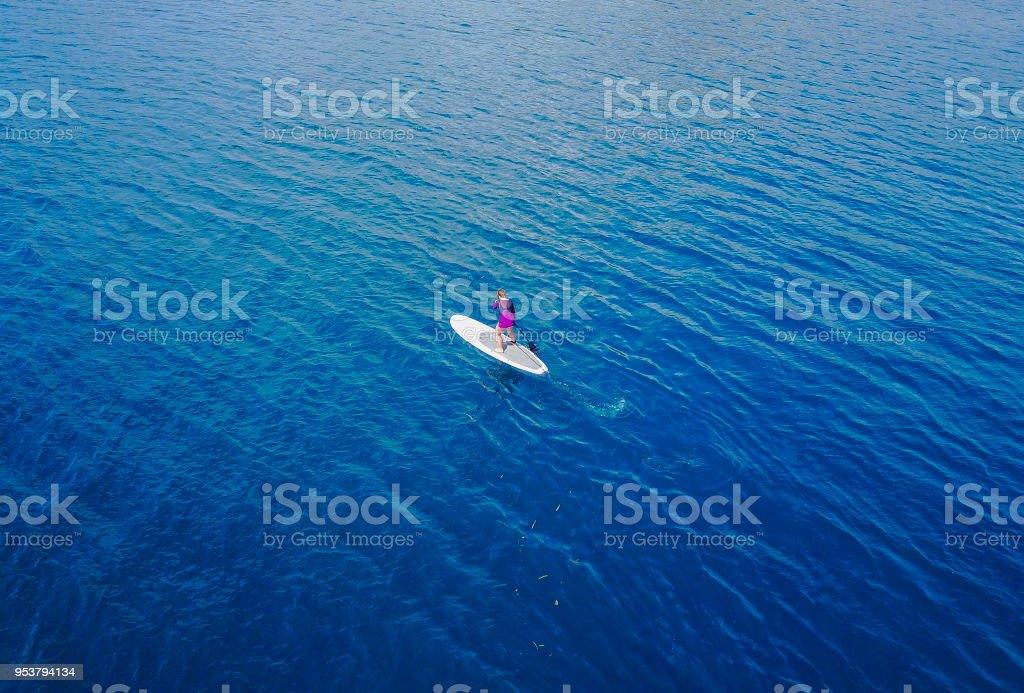Luftaufnahme von unbekannten Frauen touristischen Paddeln ein Surfbrett bis Mitte des Meeres. – Foto