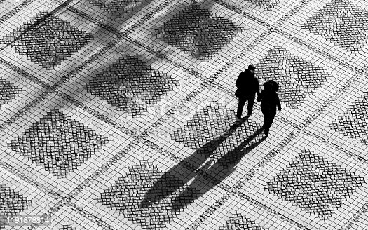 Black and white toned image depicting an aerial high angle view of a couple (a man and a woman) walking and holding hands across a pedestrianised city square. The sun is low in the sky and the couple cast long shadows across the paved square behind them. Room for copy space.