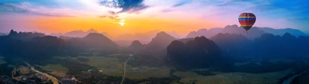 luftaufnahme von vang vieng mit bergen und ballon bei sonnenuntergang. - sambia stock-fotos und bilder
