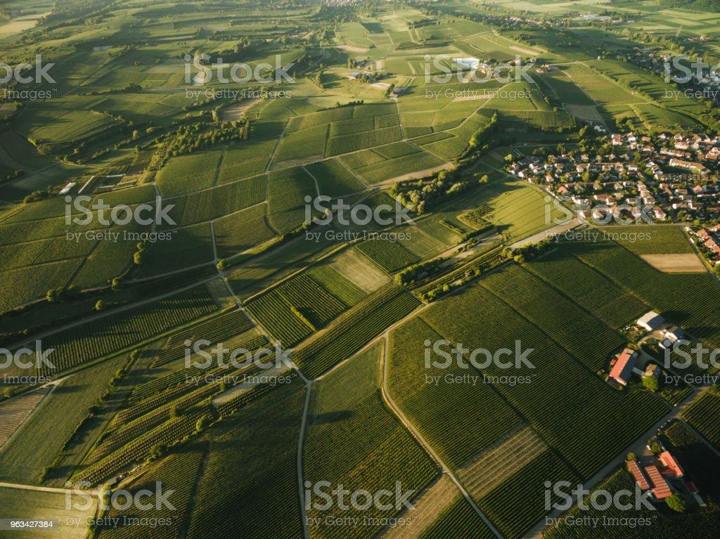 widok z lotu ptaka na wioskę otoczoną polami uprawy rolnej, - Zbiór zdjęć royalty-free (Architektura)