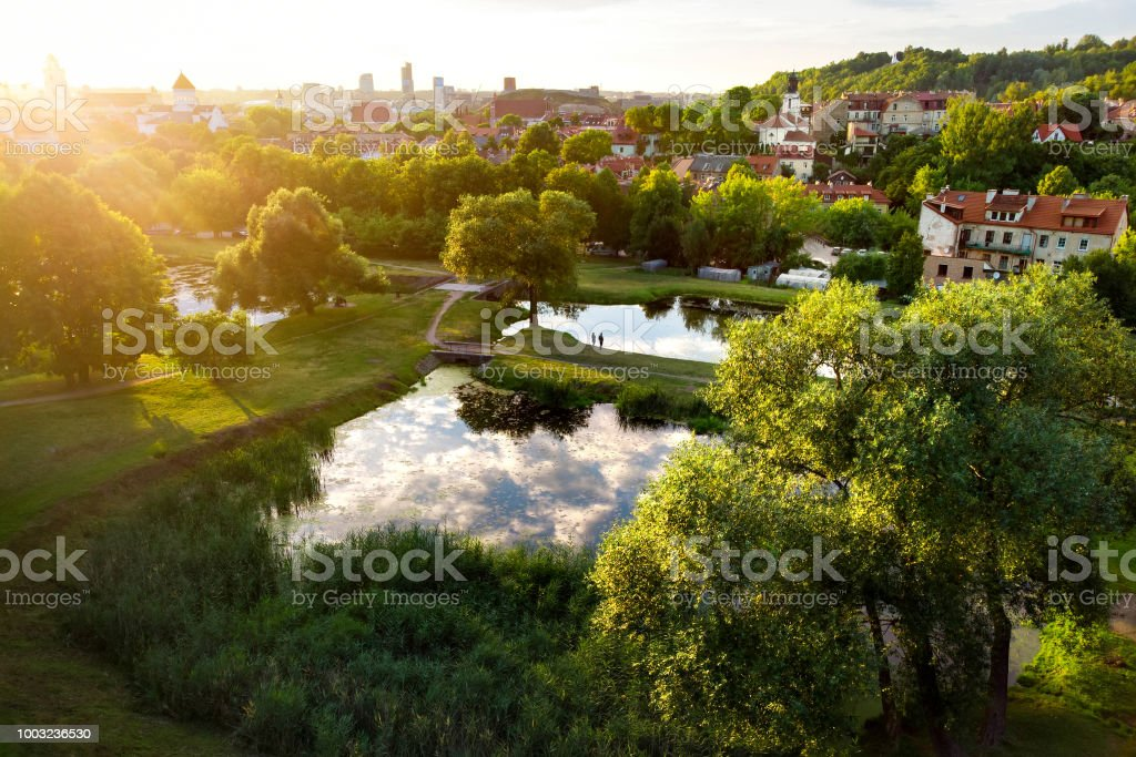 Aerial view of Vilnius cityscape shot from Subaciaus viewpoint on sunset. Clouds reflecting in three ponds of Lithuania capital's city park. stock photo