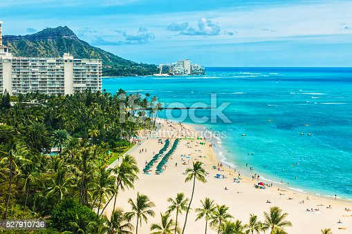An aerial photo of Waikiki beach.  There are several tall buildings visible both in the foreground and in the background.  There is a swimming pool with clear blue water in the foreground, surrounded by palm trees.  There is a parking lot with several cars in it beside a neat hedge.  On the shore there are palm trees scattered.  There is a beach with white sand and many people on it.  Small structures are visible on the beach, some white and others red.  Some people are swimming in the blue ocean.  In the distance Diamond Head mountain can be seen.