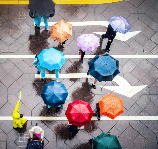 Aerial view of walking people using colorful umbrellas in rain stock photo