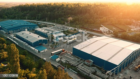 Aerial view of warehouse storages or industrial factory or logistics center from above. Aerial view of industrial buildings and equipment machines at sunset