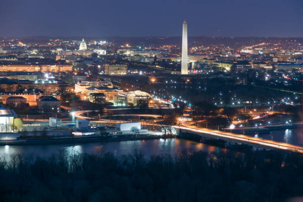 Aerial View of Washington DC at Night Illuminated Washington DC at night with the Washington Monument and the US Capitol and the Potomac River in the foreground washington dc stock pictures, royalty-free photos & images