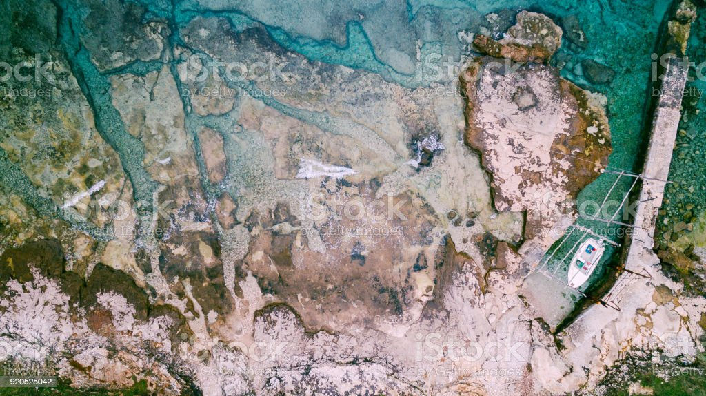 Aerial view of waves break on rocky beach. Sea waves on the beautiful colorful rocky beach. Aerial view drone 4k shot. Zoom in stock photo