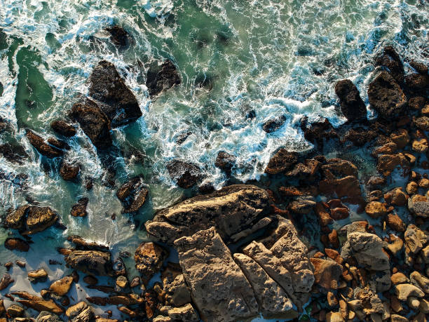 Aerial View of Waves breaking on Rocky Coastline Aerial View of Waves breaking on Rocky Coastline rocky coastline stock pictures, royalty-free photos & images