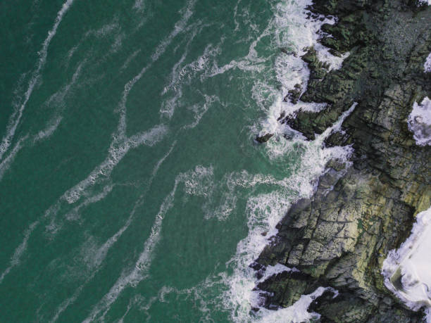 Aerial View of Waves Hitting Rocks stock photo