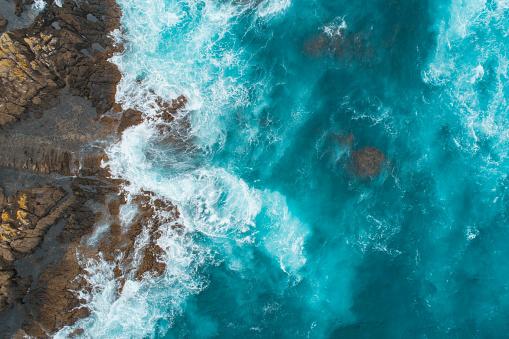 Aerial view of waves splashing on beach.